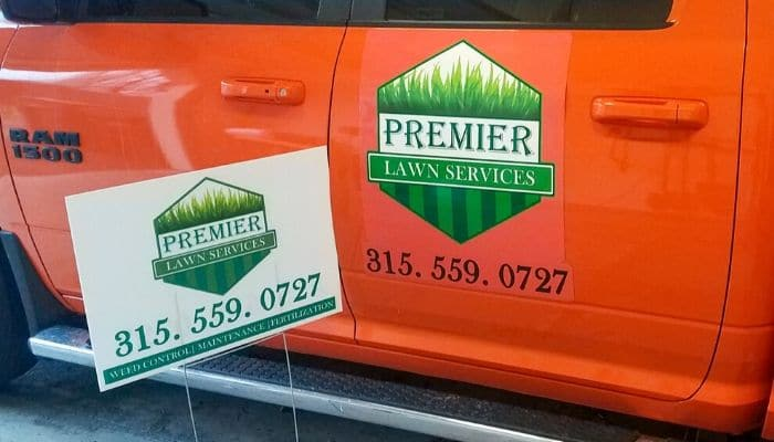 A company truck and yard sign that have the Premier Lawn Services logo and contact information.