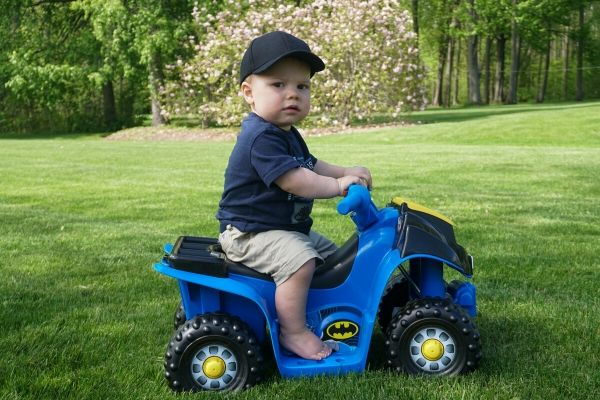 The toddler aged son of the owner of Premier Lawn Services rides a toy car in their well maintained lawn.