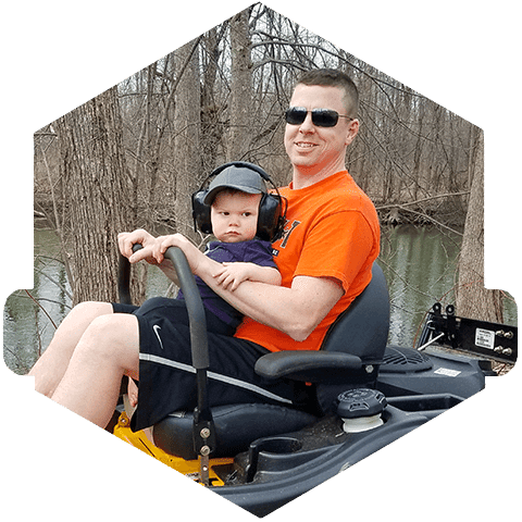 The owner and his son ride together on a professional grade lawn mower.