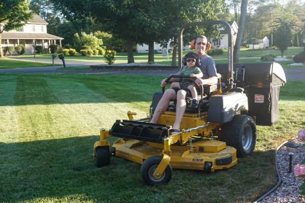 Jim Barrett, owner of Premier Lawn Services and his son sitting on a commercial lawn mower on a residential property.