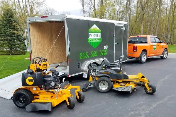 The Premier Lawn Services company truck and trailer with the company's logo and contact information.  Two professional grade lawn mowers can be seen in the foreground.
