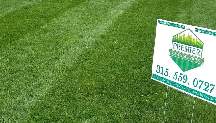 A healthy green lawn with a yard sign that has the Premier Lawn Services Logo and contact information.