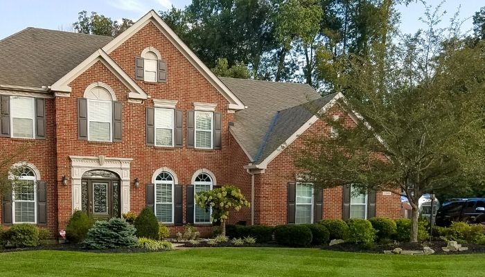 A customer home with well defined and maintained flower beds lining the home.