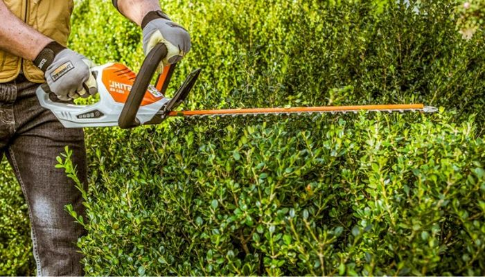 A team member used a hedge trimmer to prune bushes.